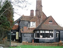 Peg tiles cover the roof slopes of this Arts & Crafts house in North London and hanging tiles cover its gables.